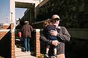 """ONEONTA, AL – DECEMBER 12, 2017: Oneonta resident Bart Cornelius exits a polling station with his grandson at the Blount County Human Resources Center after voting in Alabama's Special General Election for the United States Senate.  """"I vote conservative because of the Supreme Court. That's my main concern. I don't know how I feel about Roy Moore honestly. But I know men are men, and I hate to see him crucified because of his testosterone."""" CREDIT: Bob Miller for The New York Times"""