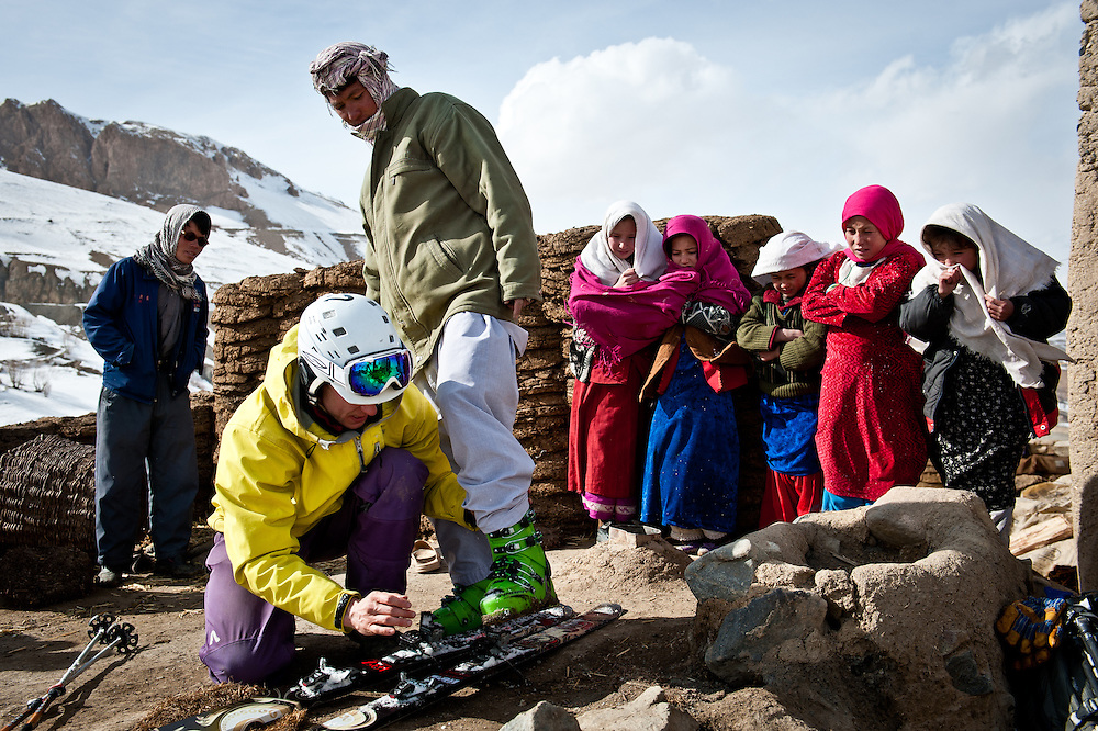 John Trousdale fits his ski boots onto a Jawkar villager's feet as a group of young girls look on.