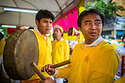 14 OCTOBER 2012 - BANGKOK, THAILAND:  Men play gongs and drums in the merit making area on the first day of the Vegetarian Festival in Bangkok's Chinatown. The Vegetarian Festival is celebrated throughout Thailand. It is the Thai version of the The Nine Emperor Gods Festival, a nine-day Taoist celebration beginning on the eve of 9th lunar month of the Chinese calendar. During a period of nine days, those who are participating in the festival dress all in white and abstain from eating meat, poultry, seafood, and dairy products. Vendors and proprietors of restaurants indicate that vegetarian food is for sale by putting a yellow flag out with Thai characters for meatless written on it in red.     PHOTO BY JACK KURTZ