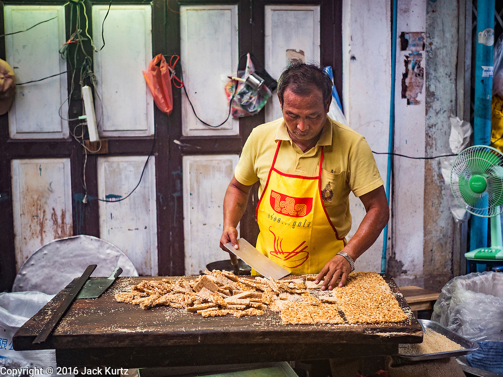 04 OCTOBER 2016 - BANGKOK, THAILAND:  A vendor makes Chinese peanut and sesame seed snacks at the Vegetarian Festival at the Chit Sia Ma Chinese shrine in Bangkok. The Vegetarian Festival is celebrated throughout Thailand. It is the Thai version of the The Nine Emperor Gods Festival, a nine-day Taoist celebration beginning on the eve of 9th lunar month of the Chinese calendar. During a period of nine days, those who are participating in the festival dress all in white and abstain from eating meat, poultry, seafood, and dairy products. Vendors and proprietors of restaurants indicate that vegetarian food is for sale by putting a yellow flag out with Thai characters for meatless written on it in red.    PHOTO BY JACK KURTZ