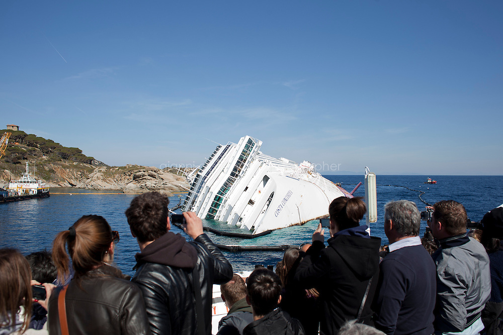 GIGLIO (GR), ITALY - 9 APRIL, 2012: Tourists on the ferry from Porto Santo Stefano to Giglio photograph the Costa Concordia cruise ship capsized on January 14th as they approach the Tuscan island. Giglio, a Tuscan island famous for its pristine waters and quiet living style, faces the challenges of starting a tourist season with a 225,000-tonne ship stuck at the entrance of its tiny port. Months after the Costa Concordia shipwreck, the Tuscany Region and Ministry for Tourism financed a 50,000-euro promotional campaign to encourage visitors to go to Giglio for the summer, while islanders are creating new walking paths and wine tasting tours to diversify their offer, trying to take advantage of the popularity that the tiny island has gained globally last January. The new attraction on Giglio has already caused an increase in the number of tourists who go to the island just for one day. <br /> <br /> Ph. Gianni Cipriano for The New York Times