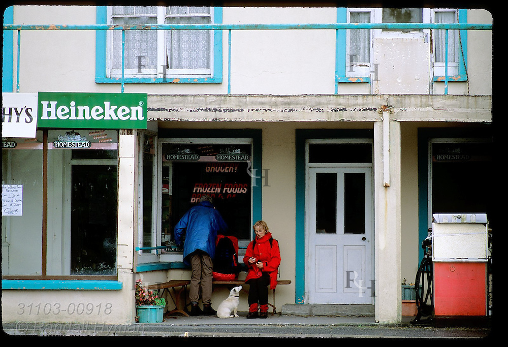 Backpacking couple sits out rainstorm on grocery store porch as dog begs snack; Ardgroom, Beara Peninsula, Ireland.