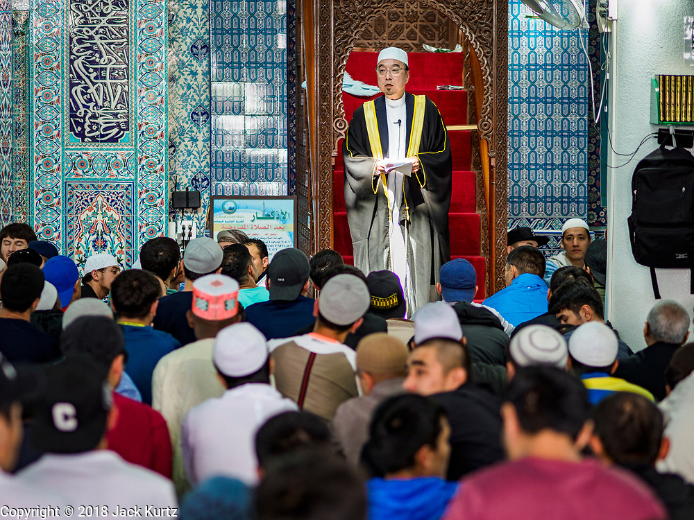 "15 JUNE 2018 - SEOUL, SOUTH KOREA: The Imam delivers the ""Khutbah,"" or sermon, at Seoul Central Mosque on Eid al Fitr, the Muslim Holy Day that marks the end of the Holy Month of Ramadan. There are fewer than 100,000 Korean Muslims, but there is a large community of Muslim immigrants in South Korea, most in Seoul. Thousands of people attend Eid services at Seoul Central Mosque, the largest mosque in South Korea.   PHOTO BY JACK KURTZ"