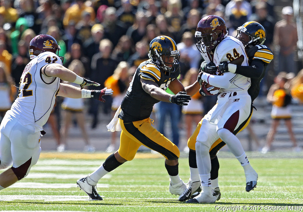 September 22 2012: Iowa Hawkeyes linebacker Christian Kirksey (20) and defensive back B.J. Lowery (19) pull down Central Michigan Chippewas wide receiver Titus Davis (84) after a catch during the first half of the NCAA football game between the Central Michigan Chippewas and the Iowa Hawkeyes at Kinnick Stadium in Iowa City, Iowa on Saturday September 22, 2012. Central Michigan defeated Iowa 32-31.
