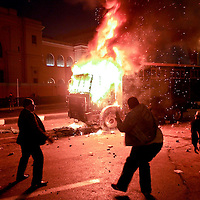 Demonstrators throw objects at a police vehicle on fire outside of the Egyptian Museum in downtown Cairo, Egypt. January 2011.