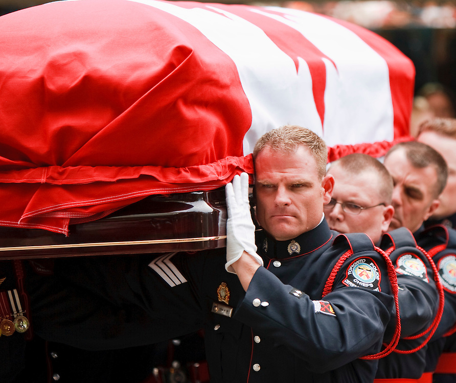 Toronto, Ontario ---11-08-27--- A police honour guard carries the casket of Jack Layton from Roy Thompson Hall in Toronto, Ontario following a state funeral for the late NDP leader August 27, 2011. <br /> AFP/GEOFF ROBINS/STR