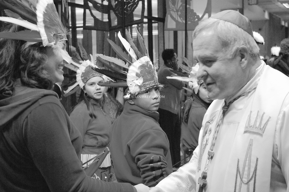 Archbishop Robert J. Carlson greeted Elizabeth Morales, a parishioner at St. Vincent Catholic Church, while Melissa Flores (St. Cecilia) and Edward Morales (St. Cecilia) look on. They belong to a group of religious dancers called The Matachines, which danced at the rally.. .