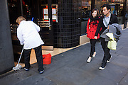 Young Chinese couple walk past a woman mopping floor of Angus Steak House in Soho, on Charing Cross Road, central London.