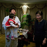 BEIJING, 25. JANUARY, 2009 :   Mr. Li, a paper factory owner, carries his grandchild   on new years' eve  in Beijing .<br /> Mr. Li, a paper factory owner, is facing one of his most difficult times .&quot; Last November the market suddenly went down ,&quot; Li says.   <br /> He had bought paper, a lot of paper, and paid 7000 Yuan/ t .<br />  Li's company buys paper from paper mills and lives from the sales to publishing houses and other companies.  Since the market's collapse , he manages to sell the paper only for 6000 Yuan/t.<br /> His clients' export business to the USA had shrunk in Southern China. Mobile phone manufacturers don't need paper for the instruction guides to their mobile phones anymore as their US clients buys less China- made mobile phones.<br />  Toy manufacturers don't need paper anymore  because Americans import less toys from China. &quot; The crisis has driven many of my clients into bancruptsy&quot;, says Li.<br />  <br /> China's Communist Party  which will celebrate its 60th anniversary in October, currently faces its biggest challenge since the beginning of the economic reforms 30 years ago  : &quot; The phase of  rapid economic growth is over. For the first time the government is threatened with a  mistrust of a wide section of the population&quot;, warns the Communist party's Shang Dewen in Beijing.   <br /> Not only the China's poorest worry about the furture, but as well China's middle class is concerned about the crisis.     1,5 Millionen university graduates didn't find a job until the end of 2008  and this summer there'll be an additional  6,1 Million new graduates. More than 12 percent of university graduates face unemployment in 2009.