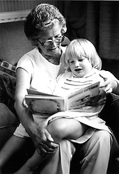 Elderly woman reading story to young granddaughter,