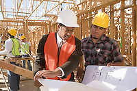 Architect and construction worker looking at blueprints