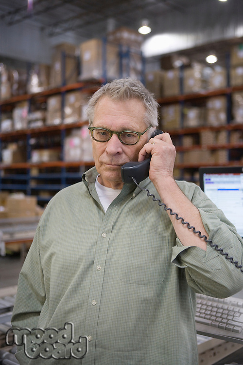 Serious man using telephone in distribution warehouse