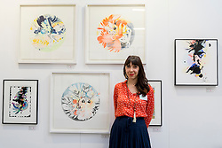 © Licensed to London News Pictures. 06/10/2016. London, UK. Artist, Blandine Bardeau shows her mixed media works at the preview of Moniker Art Fair, part of London Art Week, taking place at the Old Truman Brewery, near Brick Lane.  Now in its seventh year, the fair embraces contemporary art from emerging and established artists, the majority of whom attend the fair in person in order to meet potential collectors and to show their work. Photo credit : Stephen Chung/LNP