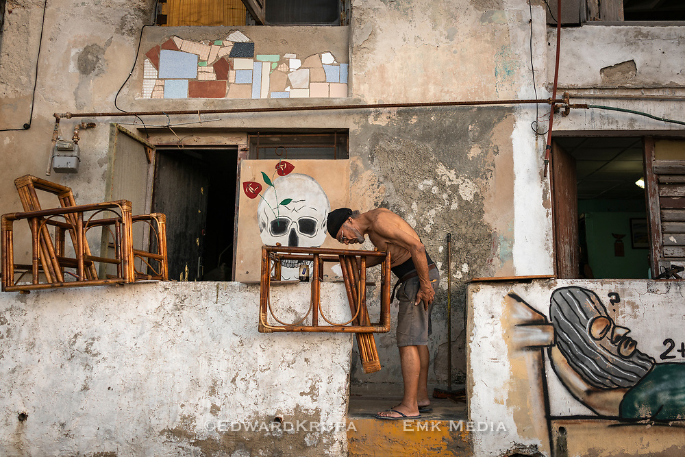 A man working on some chairs, outside a building on the Malecon in Centro Havana.