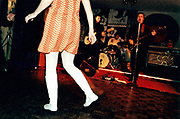 View of a woman's legs wearing white boots and dancing to the band.