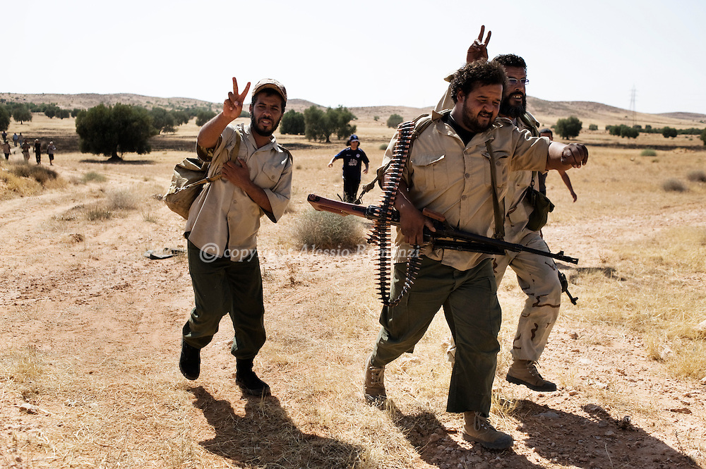 LIBYAN ARAB JAMAHIRIYA, Kikla : Libyan rebels walk to take position next to a main road leading to the last defensive position near the hill village of Kikla, southwest of Tripoli, during an offensive by forces loyal to Moamer Kadhafi on July 13, 2011.ALESSIO ROMENZI