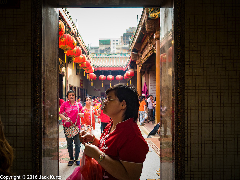 """08 FEBRUARY 2016 - BANGKOK, THAILAND:  People pray in a doorway on Chinese New Year at Wat Mangon Kamlawat, the largest Mahayana (Chinese) Buddhist temple in Bangkok during the celebration of the Lunar New Year. Chinese New Year is also called Lunar New Year or Tet (in Vietnamese communities). This year is the """"Year of the Monkey."""" Thailand has the largest overseas Chinese population in the world; about 14 percent of Thais are of Chinese ancestry and some Chinese holidays, especially Chinese New Year, are widely celebrated in Thailand.      PHOTO BY JACK KURTZ"""