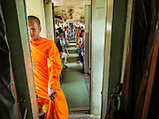 19 MARCH 2015 - BANGKOK, THAILAND:   A Buddhist monk in the passageway between cars on the third class train from Ayutthaya to Bangkok. The State Railways of Thailand (SRT), established in 1890, operates 4,043 kilometers of meter gauge track that reaches most parts of Thailand. Much of the track and many of the trains are poorly maintained and trains frequently run late. Accidents and mishaps are also commonplace. Successive governments, including the current military government, have promised to upgrade rail services. The military government has signed contracts with China to upgrade rail lines and bring high speed rail to Thailand. Japan has also expressed an interest in working on the Thai train system. Third class train travel is very inexpensive. Many lines are free for Thai citizens and even lines that aren't free are only a few Baht. Many third class tickets are under the equivalent of a dollar. Third class cars are not air-conditioned.      PHOTO BY JACK KURTZ