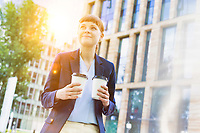 Young beautiful businesswoman holding two cups of coffee with lens flare in background