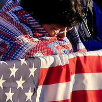 SHANKSVILLE, PA -  SEPTEMBER 11:  A visitor to the ceremony commemorating the ninth anniversary of the crash of Flight 93 near Shanvilles, Pennsylvania  huddles in a blanket to keep warm as the sunrises on September 11, 2010.  First Lady Michelle Obama And Laura Bush will be speaking to the crowd gathered to honor the victims of the terrorist attacks.   (Photo by Archie Carpenter/Getty Images)