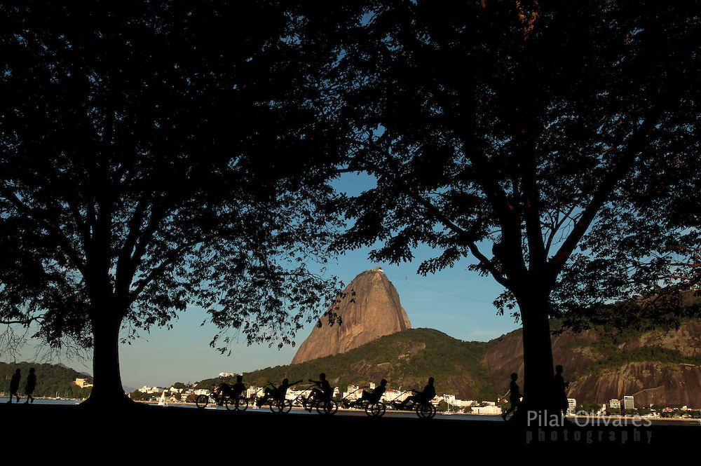 People ride a special bicycle for five along the Guanabara bay, with the Sugar Loaf mountain in the background, in Rio de Janeiro, July 29, 2012. Photo by: Pilar Olivares