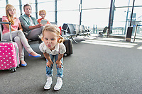 Cute little girl playing and making funny face in airport while waiting for boarding