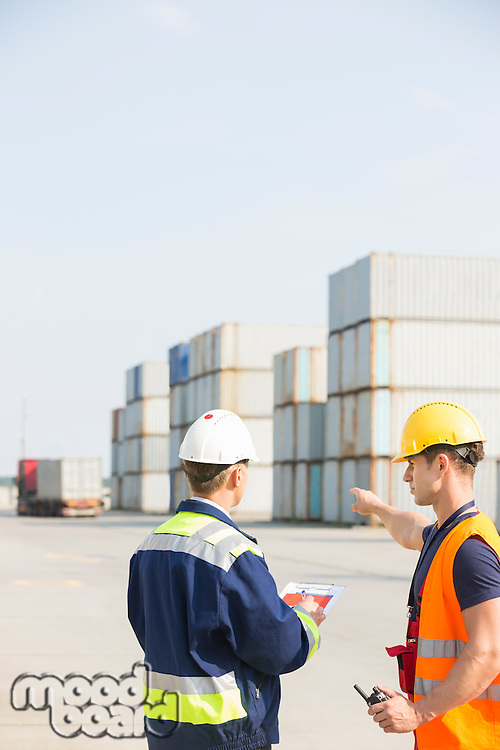 Rear view of male workers discussing in shipping yard