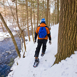 Snowshoers next to the Indian Head River at the Tucker Preserve in Pembroke, Massachusetts.  Wildlands Trust of Southeastern Massachusetts.