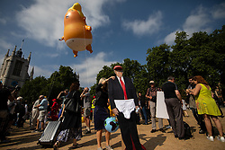© Licensed to London News Pictures . 13/07/2018. London, UK. A cardboard cut-out of Donald Trump is sited in Parliament Square as an inflatable Donald Trump blimp depicting the US president as a nappy wearing baby is launched over Westminster. Demonstrators protest against a visit by US President Donald Trump to the UK . Photo credit: Joel Goodman/LNP