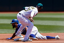 OAKLAND, CA - JULY 28:  Danny Santana #38 of the Texas Rangers is tagged out attempting to steal second base by Jurickson Profar #23 of the Oakland Athletics during the first inning at the RingCentral Coliseum on July 28, 2019 in Oakland, California. (Photo by Jason O. Watson/Getty Images) *** Local Caption *** Danny Santana; Jurickson Profar