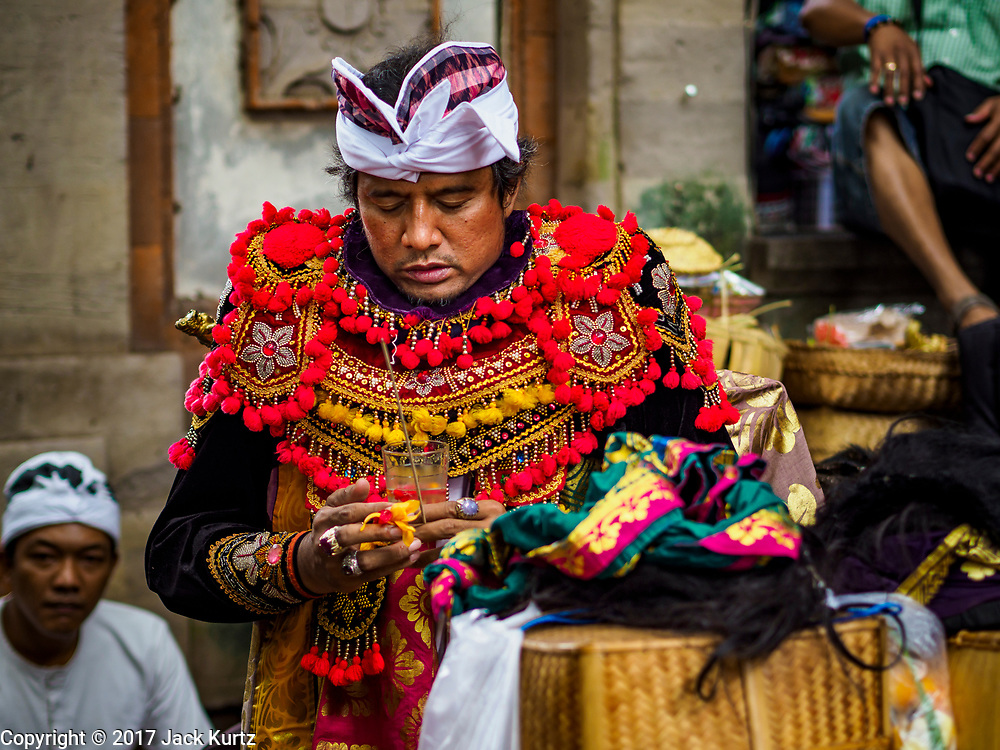 "02 AUGUST 2017 - UBUD, BALI, INDONESIA: A traditional Balinese dancer puts of his costume before performing during the ""Merchants' Day"" ceremony at the Pura (Temple) Melanting Pasar Ubud, the small Hindu temple in the Ubud market. It's a day that merchants throughout Ubud come to the temple to make offerings and pray for prosperity.    PHOTO BY JACK KURTZ"