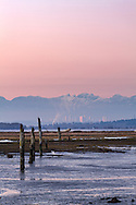 The tide flats at Crescent Beach (Blackie Spit) with the skyline of Burnaby and the North Shore Mountains in the background. Photographed from Blackie Spit in Surrey, British Columbia, Canada.