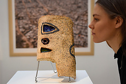 """© Licensed to London News Pictures. 12/05/2017. London, UK.   A staff member views """"Bomboy"""", 1978-79, by El Anatsui (Ghana) (Est. GBP 30-50k) at the preview for the first sale dedicated to Modern and Contemporary African Art at Sotheby's New Bond Street.  The sale features over 115 artworks by over 60 different artists from 14 countries across the continent. Photo credit : Stephen Chung/LNP"""
