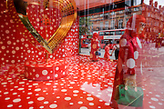 Window display in Selfridges, a collaboration between Louis Vuitton and Yakoi Kusama whose red campaign theme accompanies a life size model of the artist.