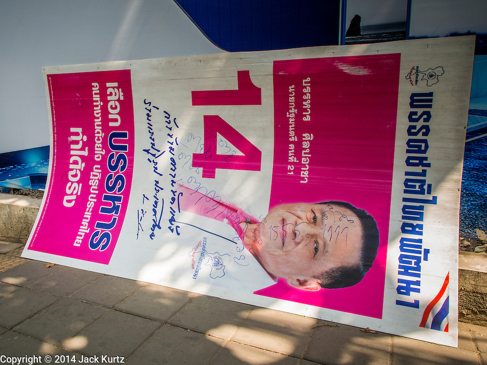 29 JANUARY 2014 - BANGKOK, THAILAND:  A defaced campaign sign on the side of a Bangkok street. Thais are supposed to vote Sunday, February 2 in a controversial national election. Anti-government protestors have vowed to disrupt the election. One person was killed and several injured in election related violence during early voting on Sunday Jan. 25. The ruling Pheu Thai party is widely expected to win the election, which is being boycotted by the Democrats and opposition parties.      PHOTO BY JACK KURTZ
