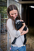Portrait of an attractive woman with baby black sheep in a rural setting.