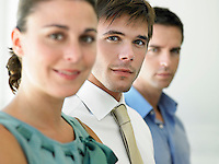 Businesswoman and two businessmen focus on man portrait