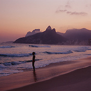 A young boy on the waters edge in a late afternoon beach scene at Arpoador Beach with Ipanema and Leblon beaches and the twin peaks of Dois Irmaos in the distance, Rio de Janeiro, Brazil. 12th July 2011. Photo Tim Clayton..