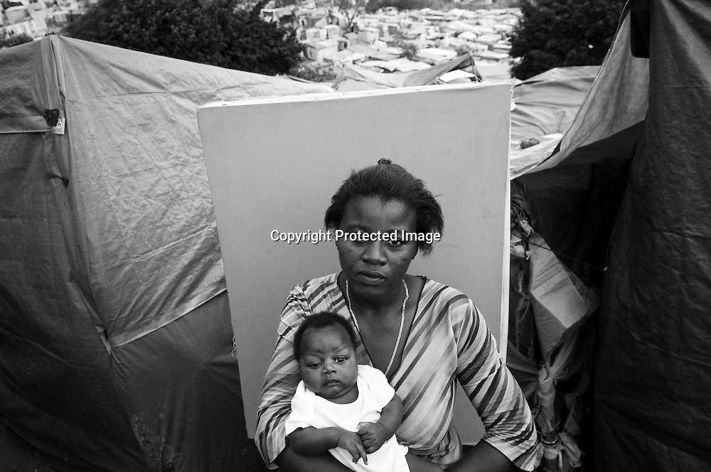 Elmina Alexis, 28, holds her baby Noyan Jean-Baptiste, 1 month old, in the Delmas 40B tent camp. The baby was just nine days old when the quake hit as the two of them napped together on a bed at home. Startled awake, Elmina rolled over onto the floor as rubble crashed down on the bed where she'd been lying. For two days she couldn't see much or hear anything, stuck under the rubble. She assumed her baby was dead. Finally her landlord was able to reach her and excavate her with just a shovel and his two hands. They found the baby, very much alive, resting on a concrete block, nearly untouched, save for a few scratches to his fingers and forehead.