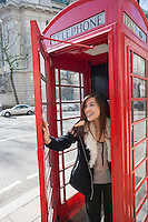 Happy young woman opening door of telephone booth at London; England; UK