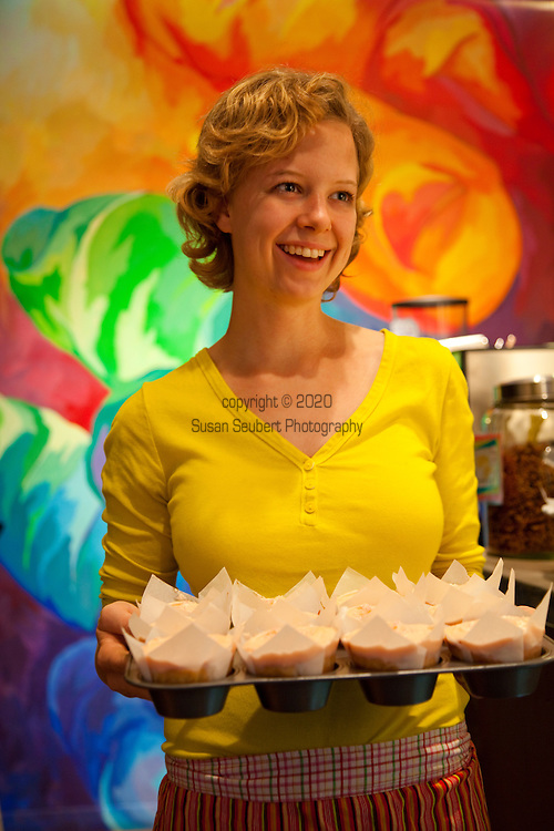Baked and Wired, a bakery and coffee and tea house in Georgetown, Washington, DC, offers up home made desserts and gourmet coffee.  One of the employees holding a pan of strawberry cupcakes.
