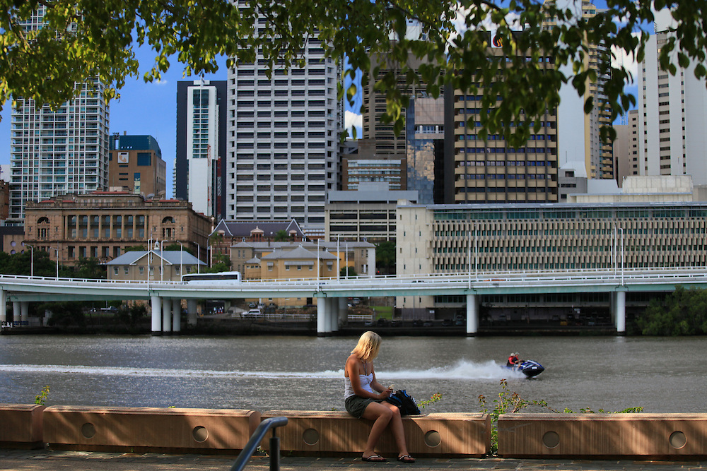 A lady enjoys a break along the wall in Brisbane's Southbank.