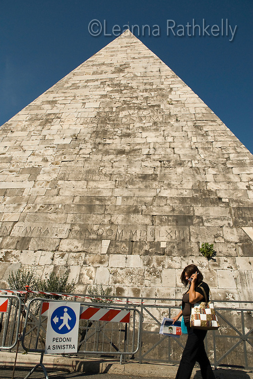 A pedestrian talks on her cell phone as she walks in front of Rome's famous Pyramid Gaius Cestius.