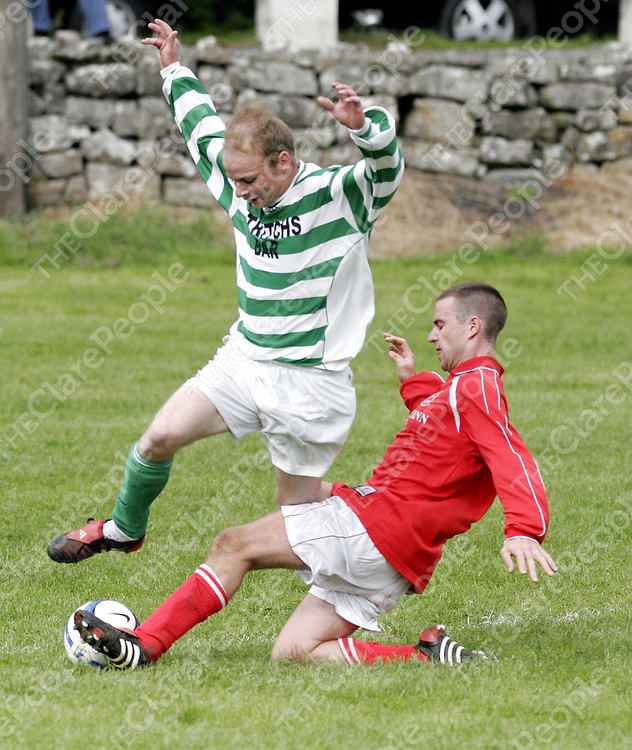 Corofin's Mark Woods gets in the tackle before Bridge Celtic's Paul McEvoy gains posession in Corofin on Sunday.<br />