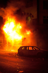 © Licensed to London News Pictures.  FILE PICTURE DATED 09/08/2011 LONDON, UK. Flames burst from the front of a shop on London Road in Croydon as a fire set in a store further down the street spreads after being set alight by looters.  Croydon was one of several London boroughs and English cities hit by a third night of rioting and looting. Photo credit: Matt Cetti-Roberts/LNP