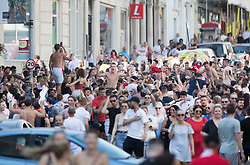 © Licensed to London News Pictures. 07/07/2018. Brighton, UK. Football fans fill a street in Brighton as they celebrate England's 2-0 quarter-final win over Sweden at the Russian World Cup. Photo credit: Peter Macdiarmid/LNP