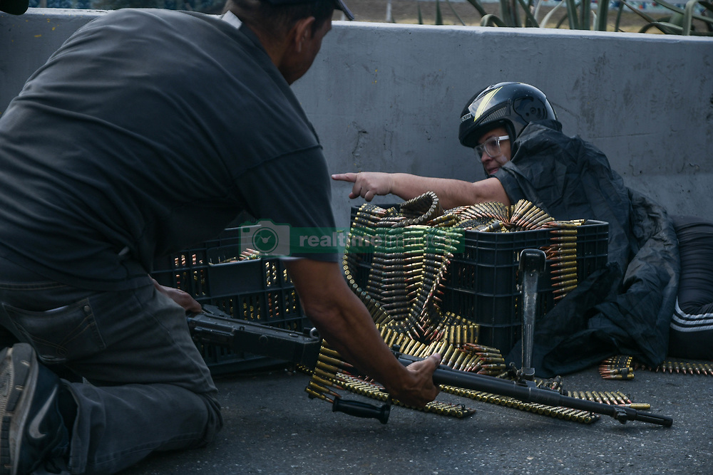 April 30, 2019 - Caracas, Miranda, Venezuela - Anti government protesters seen with machine gun bullets ready battle with pro government forces. .Venezuelan military who are supporting the Venezuelan opposition leader Juan Guaido took to the street with their weapons together with anti government protesters in a military coup against the socialist government lead by President Nicolas Maduro. (Credit Image: © Roman Camacho/SOPA Images via ZUMA Wire)