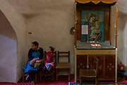 A local woman and child sitsnext to a shrine with the Virgin Mary and Jesus at St Tawdros (St Theodore's) Coptic Orthodox Christian Monastery, Luxor, Nile Valley, Egypt. The Copts are an ethno-religious group in North Africa and the Middle East, mainly in the area of modern Egypt, where they are the largest Christian denomination. Christianity was the religion of the vast majority of Egyptians from 400–800 A.D. and the majority after the Muslim conquest until the mid-10th century. Today, there are an extimated 9-15m Copts in Egypt.