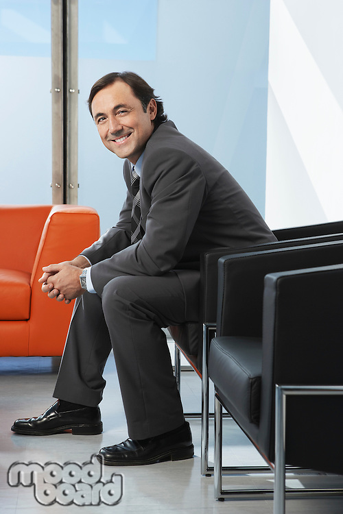 Business man sitting in leather chair in office portrait