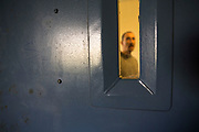 A prisoner stands outside his cell door looking through the window. HMP/YOI Portland, Dorset. A resettlement prison with a capacity for 530 prisoners. Portland, Dorset, United Kingdom.